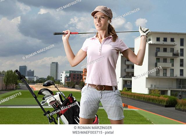 Germany, Bavaria, Munich, Young woman standing beside golf cart in city-golf ground