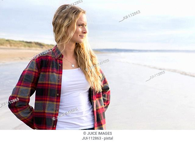 Pensive woman looking at view on sunny beach