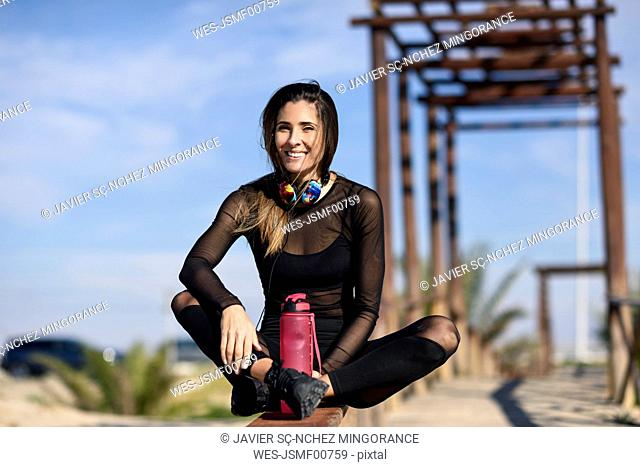 Smiling sportive woman resting after doing sports, sitting on a wooden bridge