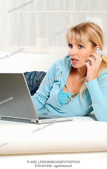 Woman with laptop computer, talking on cell phone