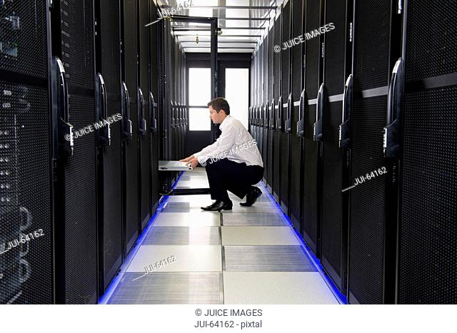 Technician replacing server in server cabinet