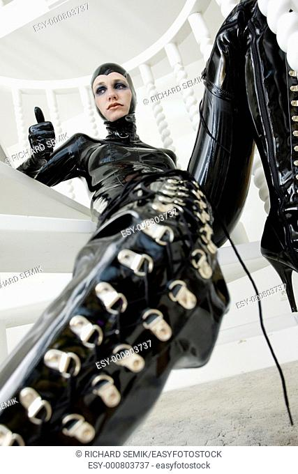 woman in latex sitting on the stairs