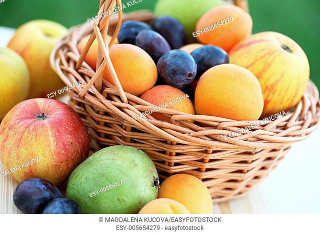 Basket filled with apples, pears, apricots and plums