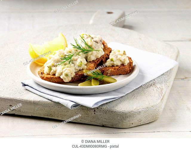 Plate of toast with herring and lemon