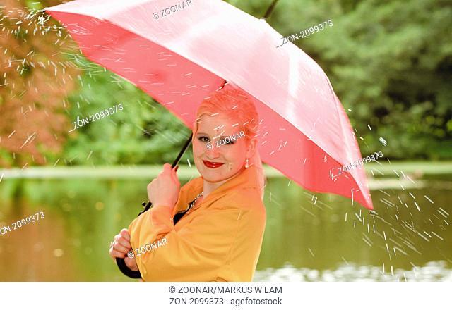 Junge blonde Frau im Regen mit Regenschirm