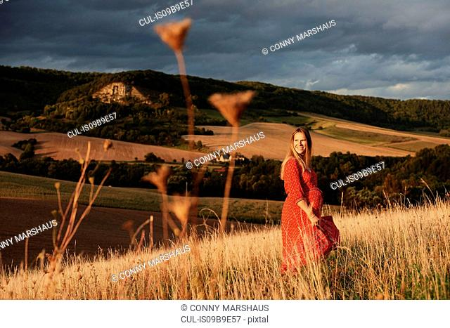Portrait of happy pregnant woman in red dress on hillside