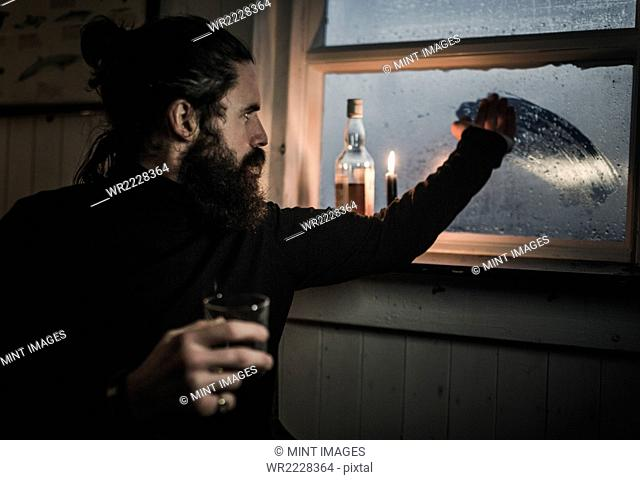 A man sitting alone in a room with a bottle of whisky and a glass, wiping condensation off the window to see outside. A lit candle