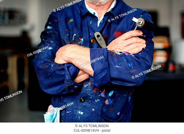 Senior craftsman with arms folded in print workshop, holding ink roller and wearing paint-splattered overalls, mid section