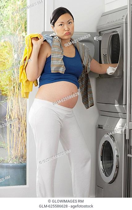 Annoyed pregnant woman holding clothes in front of a washing machine