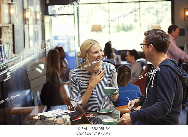 Creative businessman and businesswoman talking and drinking coffee in cafe