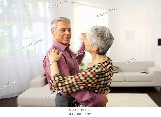 Senior couple dancing in living room, blurred motion