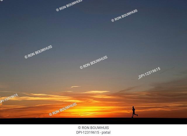 Man jogging at sunrise; Chicago, Illinois, United States of America