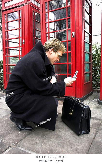 Young businessman talking on a mobile phone next to a row of British red phone boxes
