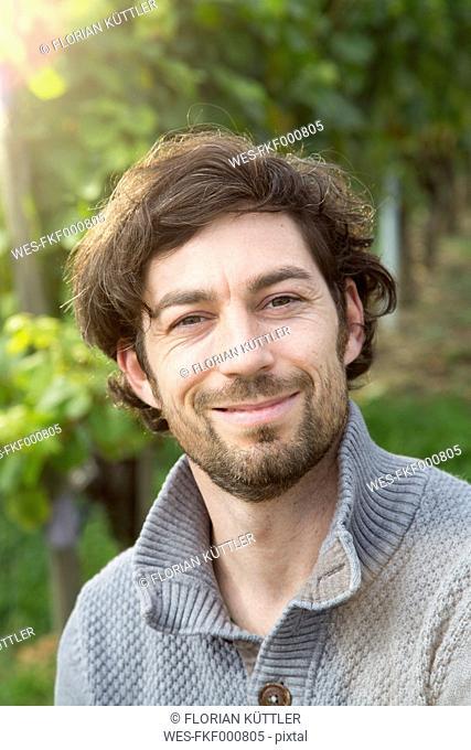 Germany, Bavaria, Volkach, portrait of winegrower in vineyard