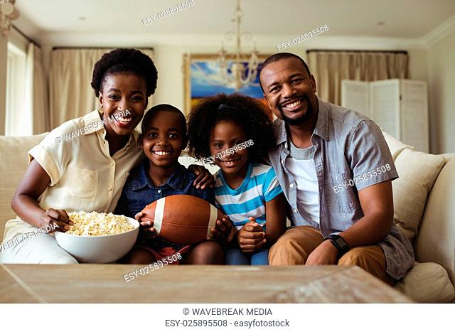 Portrait of parents and kids watching television in living room