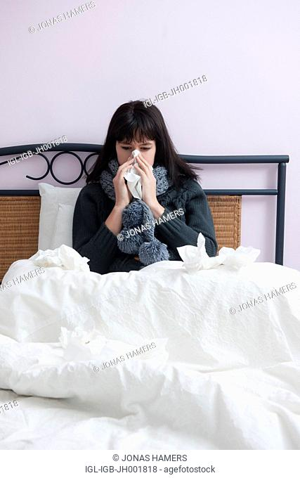 This picture shows a young caucasian woman with brown hair as she lies in her bed feeling ill or sick blowing her nose with a handkerchief