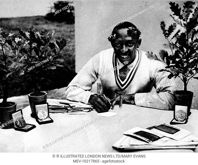 Photograph of Jesse James Cleveland Owens, the US athlete, pictured with his Olympic oak-trees and medals, 1936.  Owens won four gold medals at the the 1936...