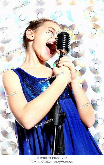 child,teen,girl,singing into a microphone,a small singer.\rthe girl in a blue dress singing karaoke\rfig. robert przybysz / forum