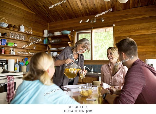 Woman pouring iced tea family cabin dining table