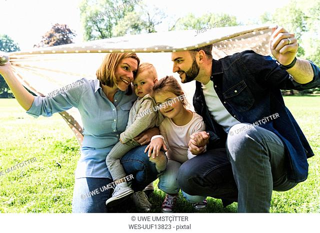 Happy family under a blanket in a park