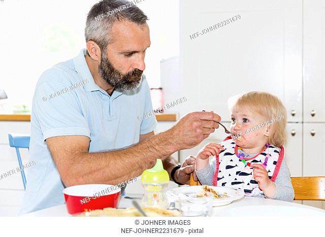 Father feeding girl