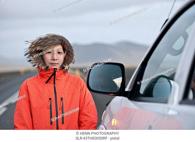 Woman standing outside car on rural road