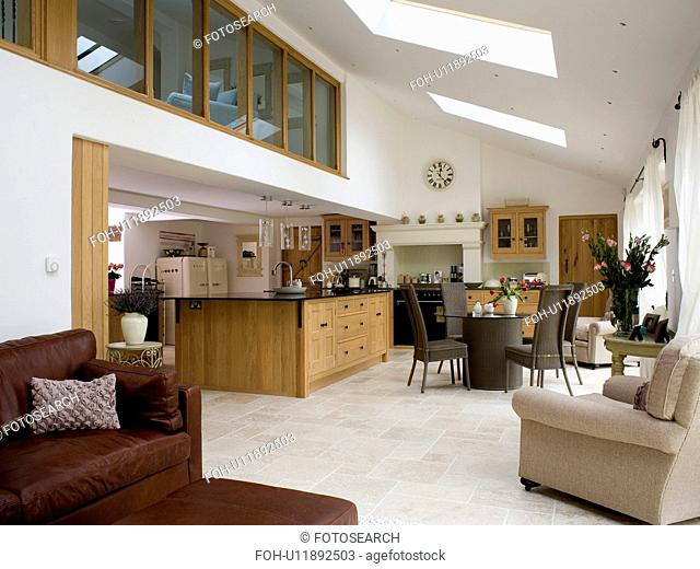 Large modern open-plan kitchen dining room extension with comfortable armchair and sofa