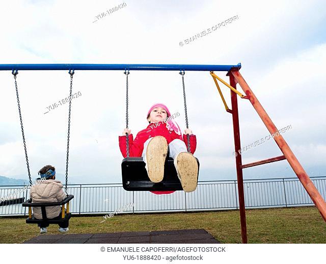 Children on the swing in winter