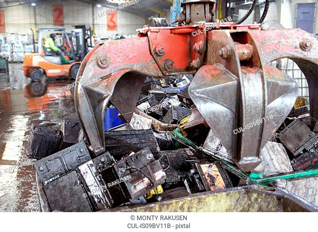 Car batteries with crane grab in vehicle battery recycling plant