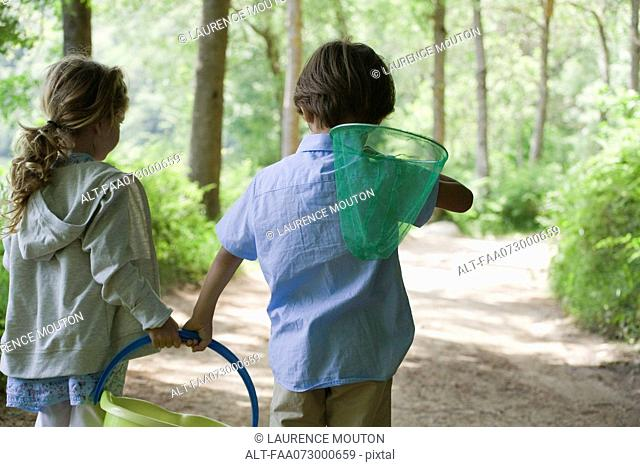 Children walking in woods together with butterfly net and bucket