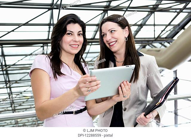 Two professional business women using a touch screen in the atrium of an office building; Edmonton, Alberta, Canada