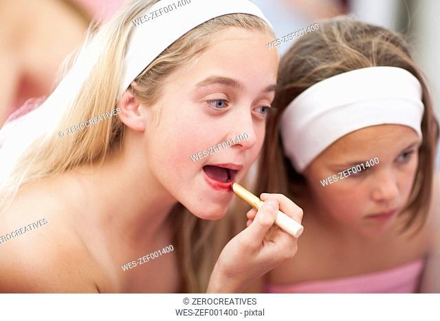 Girl on a beauty farm applying lipstick