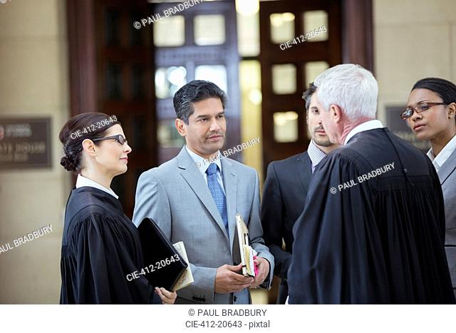 Judges and lawyers talking in courthouse