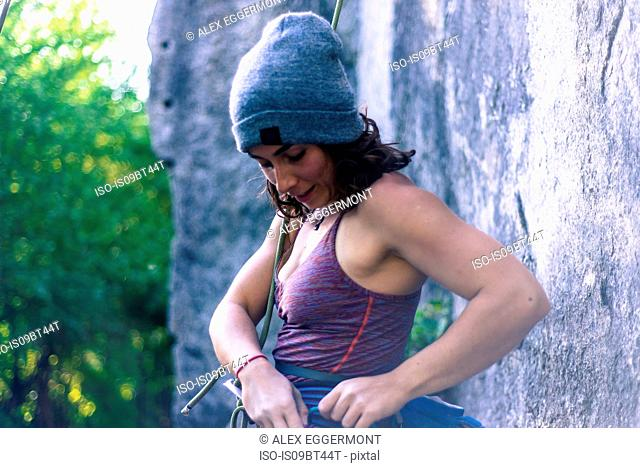 Young female rock climber preparing climbing ropes at rock face, Smoke Bluffs, Squamish, British Columbia, Canada