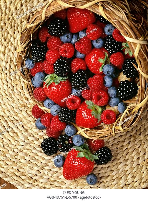 Agriculture - Strawberries, red raspberries, blackberries and blueberries in a cornucopia basket