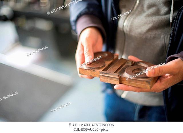Mans hands holding traditional letterpress numerals workshop