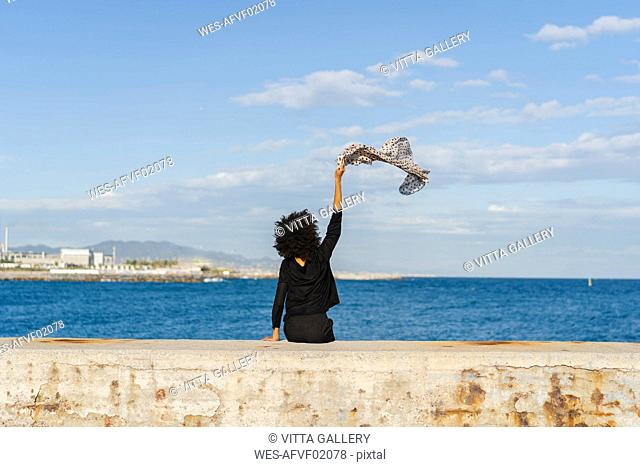 Spain, Barcelona, back view of woman dressed in black sitting on wall waving with scarf