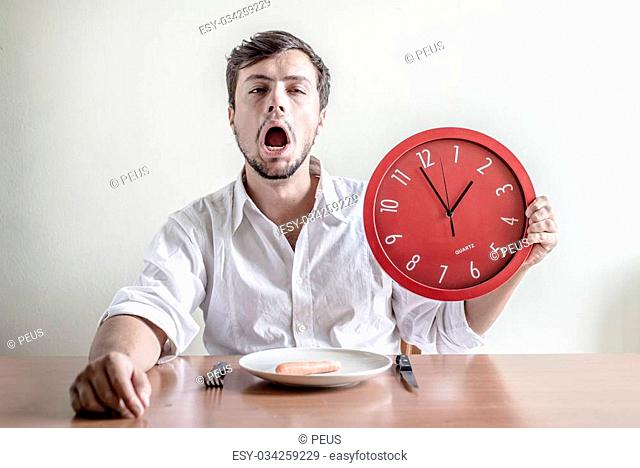 young stylish man with white shirt holding red clock behind a table