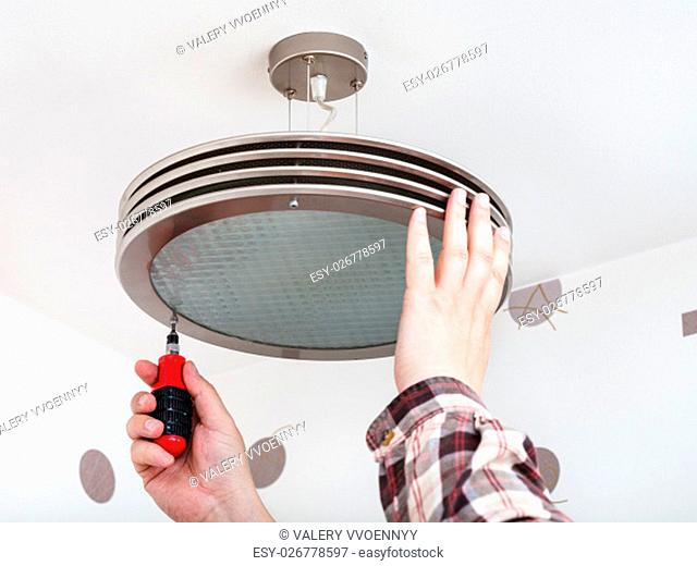 Electrician repairs round ceiling light in room