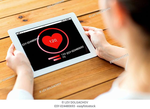 technology, people and health care concept - close up of woman with heart rate on tablet pc computer screen on wooden table