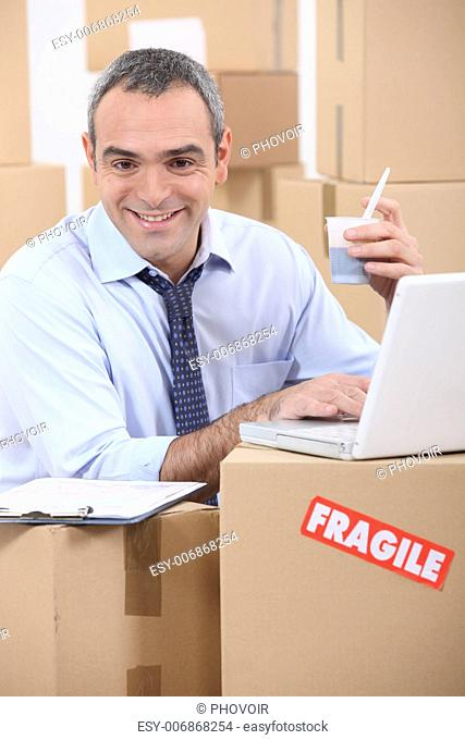 man amid cardboard boxes