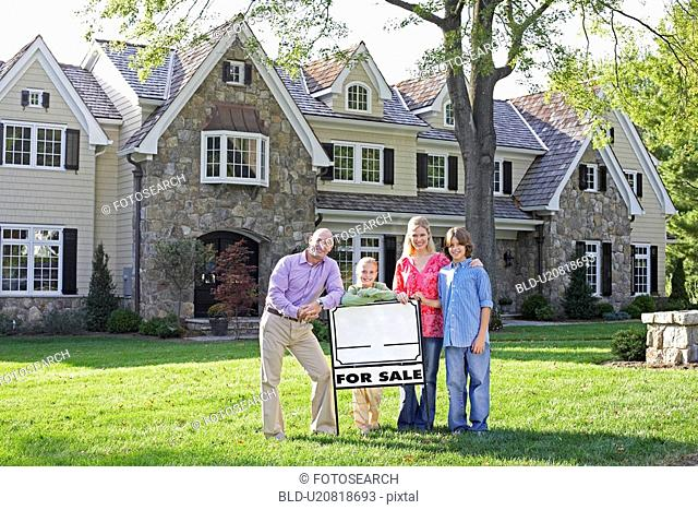 Family of four standing by sign near house, Chatham, New Jersey, USA