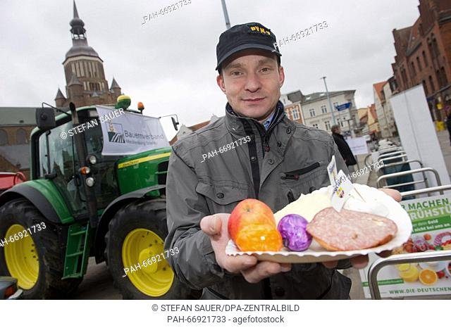 Frederick Hirzel, general manager of the Mecklenburg-Strelitz farmers' association, presents a plate with agricultural products inStralsund, Germany
