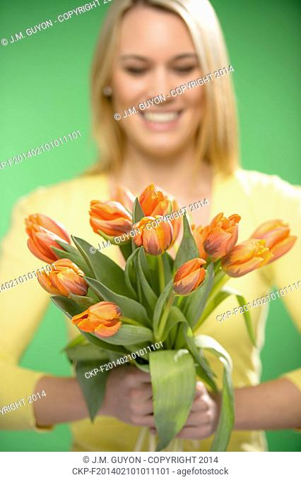 Bouquet of orange spring tulip flowers smiling woman in background