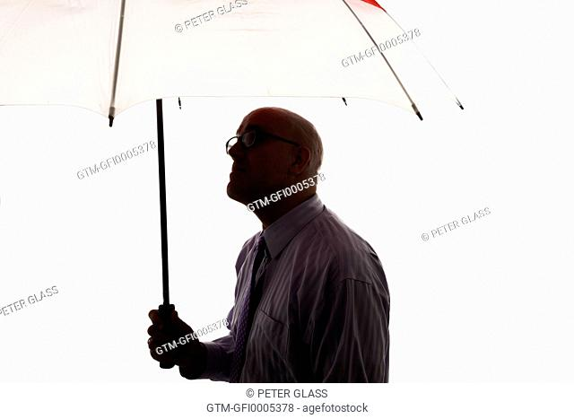 Middle-age bald man holding an umbrella
