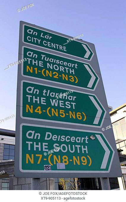 green roadsigns in dublin city centre in irish gaelic and english vertical