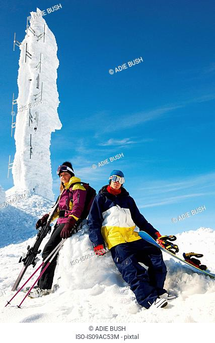Snowboarder and skier at the top of mountain with equipment, in front of ice sculpture