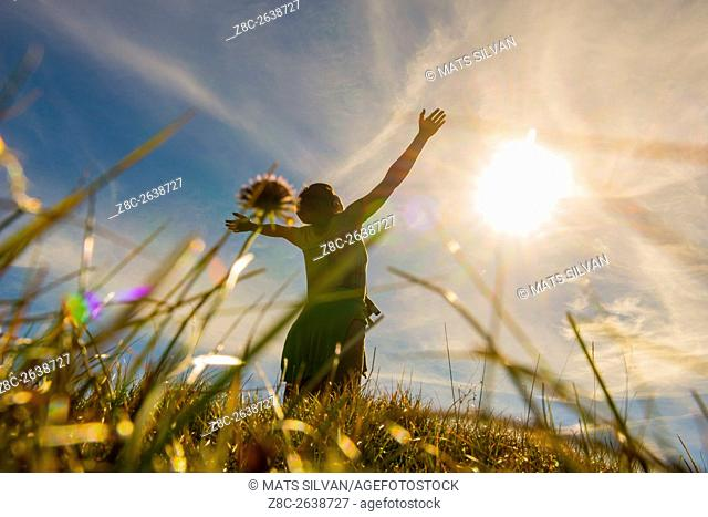 Low angle view on a woman with raised arms and grass and sunshine in Grisons, Switzerland