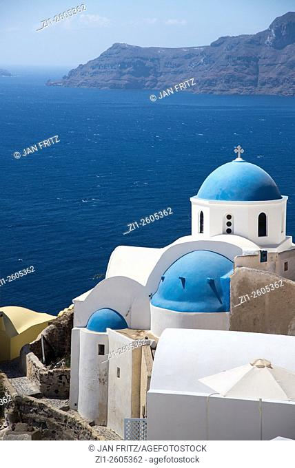 White church with blue chapel and caldera at Santorini in Greece