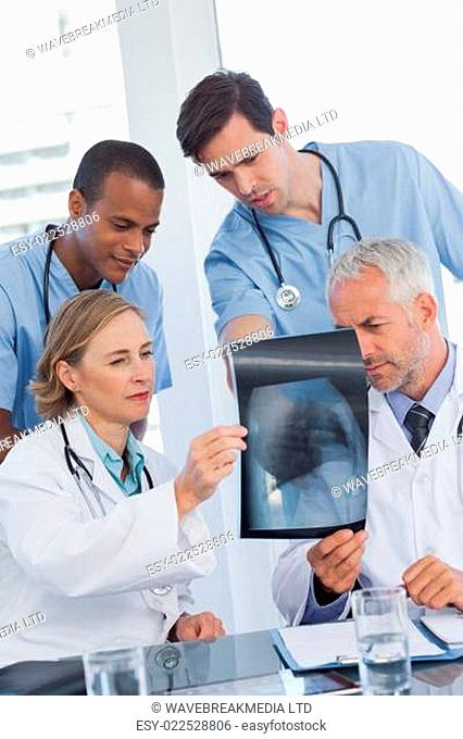 Serious medical team examining radiography in office